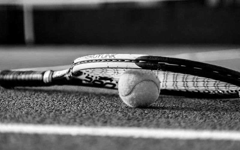 Raqueta con pelota sobre imagen en blanco y negro